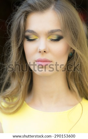Portrait of dreaming sensible young blonde lady with bright makeup and curly hair and closed eyes, vertical background - stock photo