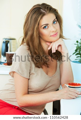 Portrait of dreaming  woman  holding coffee cup sitting near a window at the kitchen interior. Close up smiling female face.