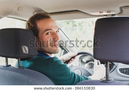 portrait of driver in the car or taxi, young caucasian man - stock photo
