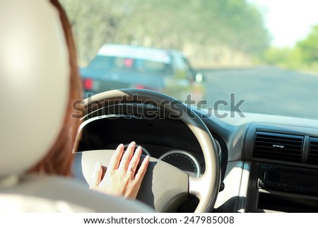 portrait of driver use horn to warn car in front of her - stock photo
