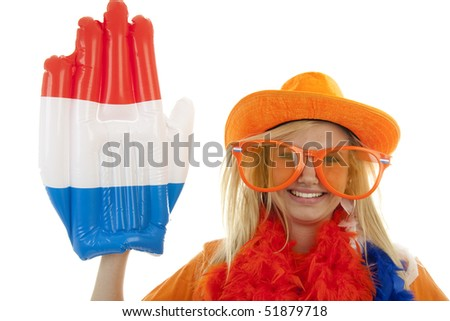 portrait of Dutch soccer fan in orange outfit with big glasses, hat and big hand over white background