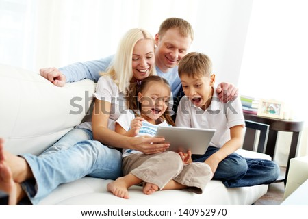 Portrait of ecstatic family with two children looking at something funny in touchpad - stock photo