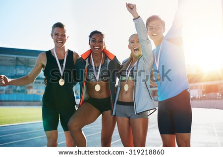 Portrait of ecstatic young athletes together with medals. Group of runners standing together smiling with their hands raised in excitement on racetrack on a bright sunny day. - stock photo