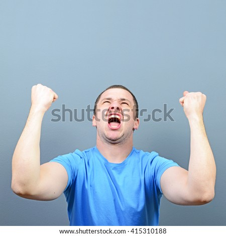 Portrait of ecstatic young man celebrating victory or win against gray background - stock photo
