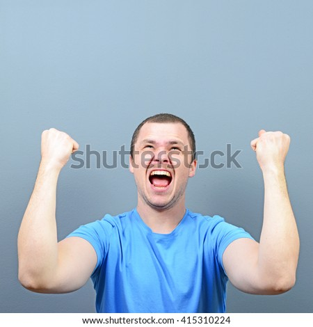 Portrait of ecstatic young man celebrating victory or win against gray background