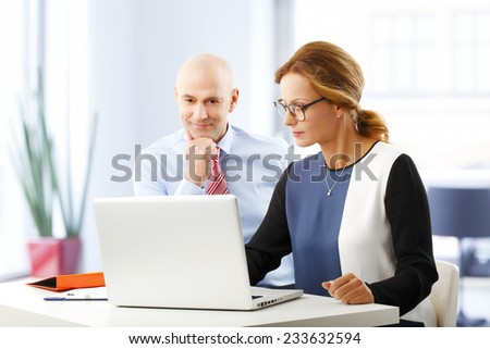 Portrait of efficiency business people analyzing data on laptop, while sitting at desk in bank. - stock photo