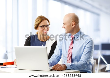 Portrait of efficiency sales team sitting at desk in front of laptop and consulting. Teamwork at office.  - stock photo
