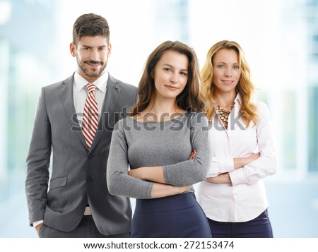 Portrait of efficiency sales team standing at office. Young businessman and businesswoman standing with middle age sales woman and looking at camera. - stock photo