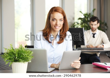 Portrait of efficiency sales woman sitting at office behind her laptop and holding hands digital tablet. Businesswoman touching the screen of tablet.  - stock photo