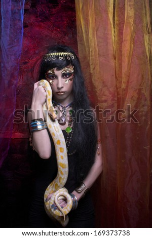 Portrait of egyptian woman posing with white snake.