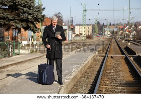 Portrait of elderly businessman holding in his hand digital tablet and checking timetable while waiting for the train at the station. - stock photo