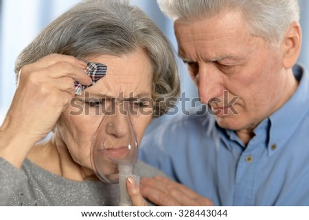 Portrait of elderly  couple making inhalation close up - stock photo