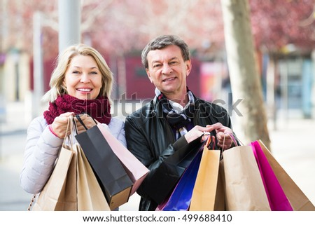 Portrait of elderly couple with shopping bags outdoors