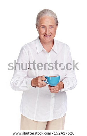 Portrait of elderly female with cup of tea looking at camera - stock photo