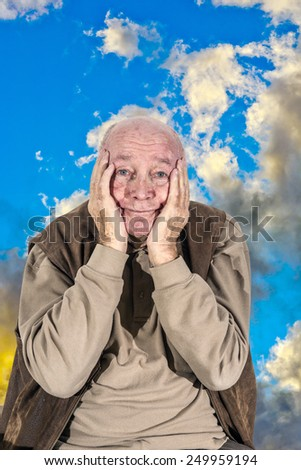 portrait of elderly funny retired man with sky background - stock photo