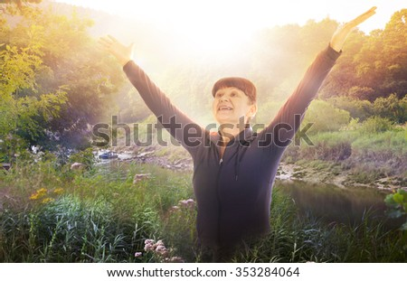 Portrait of elderly good looking woman raised her hands up towards the sun - stock photo