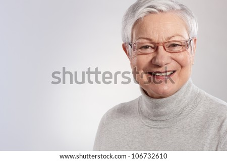 Portrait of elderly lady smiling in glasses and polo-neck sweater. - stock photo