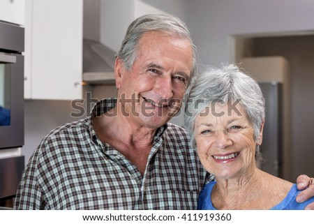 Portrait of elderly man and woman standing in the kitchen - stock photo