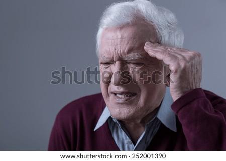 Portrait of elderly man having terrible headache - stock photo