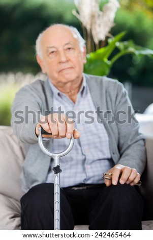 Portrait of elderly man holding metal cane while sitting on couch at nursing home porch - stock photo