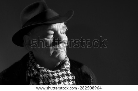 Portrait of elderly man in coat, hat and scarf on a dark background - stock photo