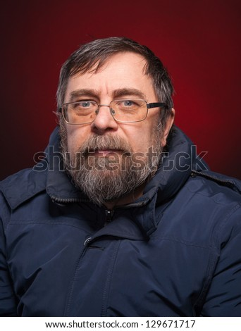 Portrait of elderly man in glasses on a red background