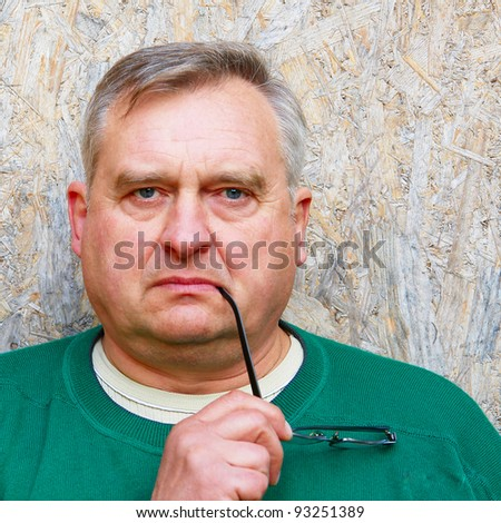 Portrait of elderly man in the background of the building slab - stock photo