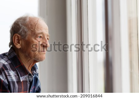 Portrait of Elderly man looking out window - stock photo