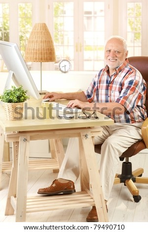 Portrait of elderly man sitting at desk using desktop computer, smiling at camera.?