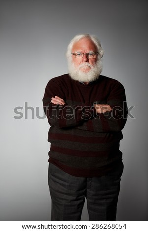 Portrait of elderly man standing with his arms crossed looking at camera seriously against grey background - stock photo