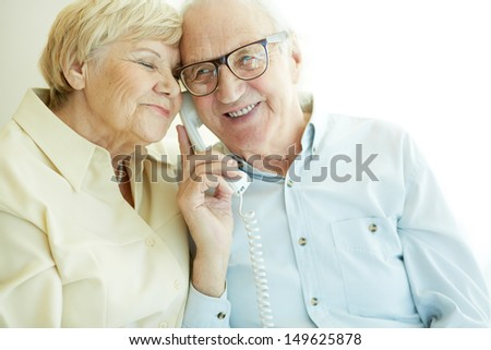 Portrait of elderly man talking on the phone with his wife near by - stock photo