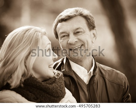 Portrait of elderly people flirting and laughing outdoors