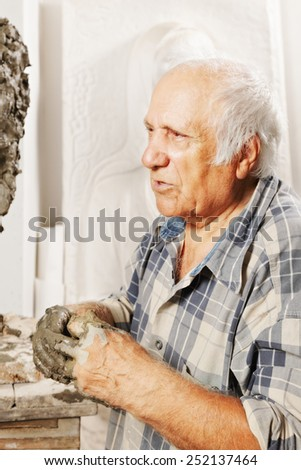 Portrait of elderly sculptor in studio - stock photo