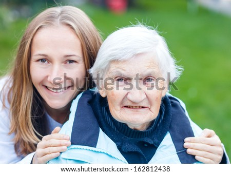 Portrait of elderly woman and her caregiver - stock photo
