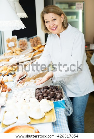 Portrait of elderly woman at confectionery display with pastry - stock photo