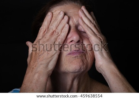 Portrait of elderly woman. Closes eyes with hands. - stock photo