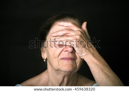 Portrait of elderly woman. Closes eyes with hands. Toned. - stock photo