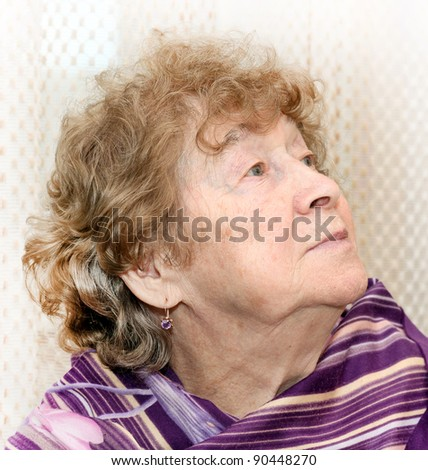 portrait of elderly woman dreaming - stock photo