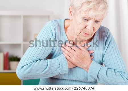 Portrait of elderly woman having heart attack - stock photo