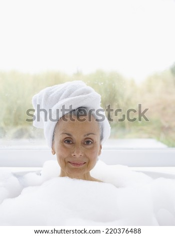 Portrait of elderly woman in bubble bath with towel wrapped around head - stock photo