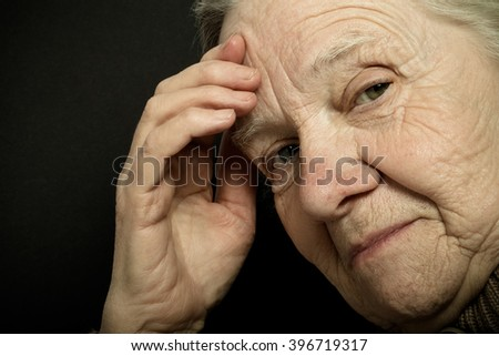 Portrait of elderly woman on dark background. Toned.