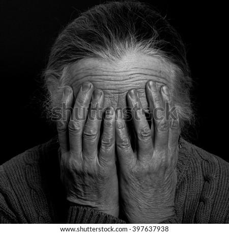 Portrait of elderly woman on dark background. Toned. - stock photo