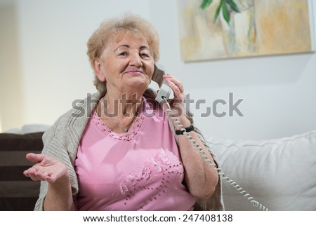 Portrait of elderly woman talking on stationary telephone - stock photo