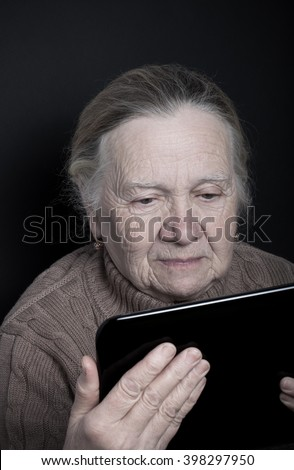 Portrait of elderly woman with tablet computer on dark background. Toned. - stock photo