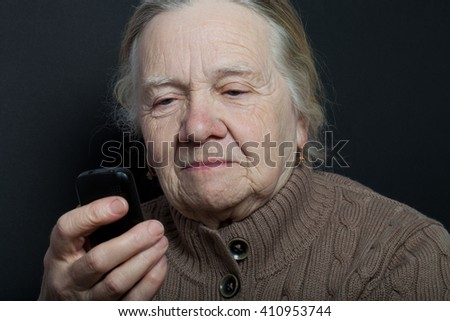 Portrait of elderly woman with telephone on dark background.