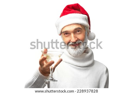 Portrait of eldery handsome caucasian man in santa's red hat is going to drink martini holding a glass smiling isolated on white background - stock photo