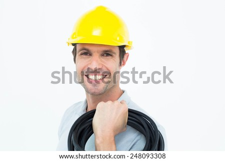 Portrait of electrician carrying wires over white background