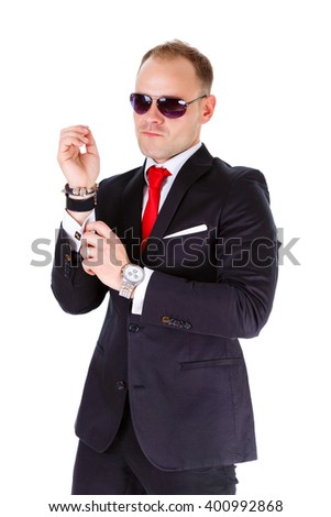 Portrait of elegant and stylish business man in black suit, red tie, white shirt and black sunglasses, adjusts his cufflinks - isolated on white background. Leather bracelet and clock on man's wrist - stock photo