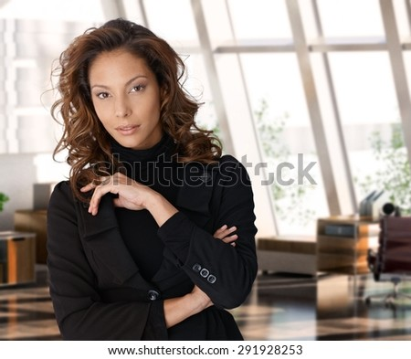 Portrait of elegant attractive businesswoman at office, standing, serious, looking at camera.
