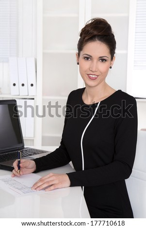 Portrait of elegant beautiful businesswoman at desk. - stock photo